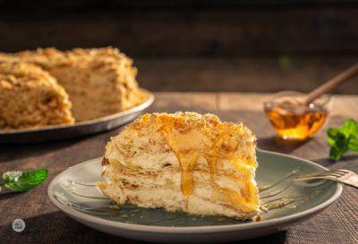 Домашна торта Наполеон, поднесена на парче, залята с мед и заснета отстрани