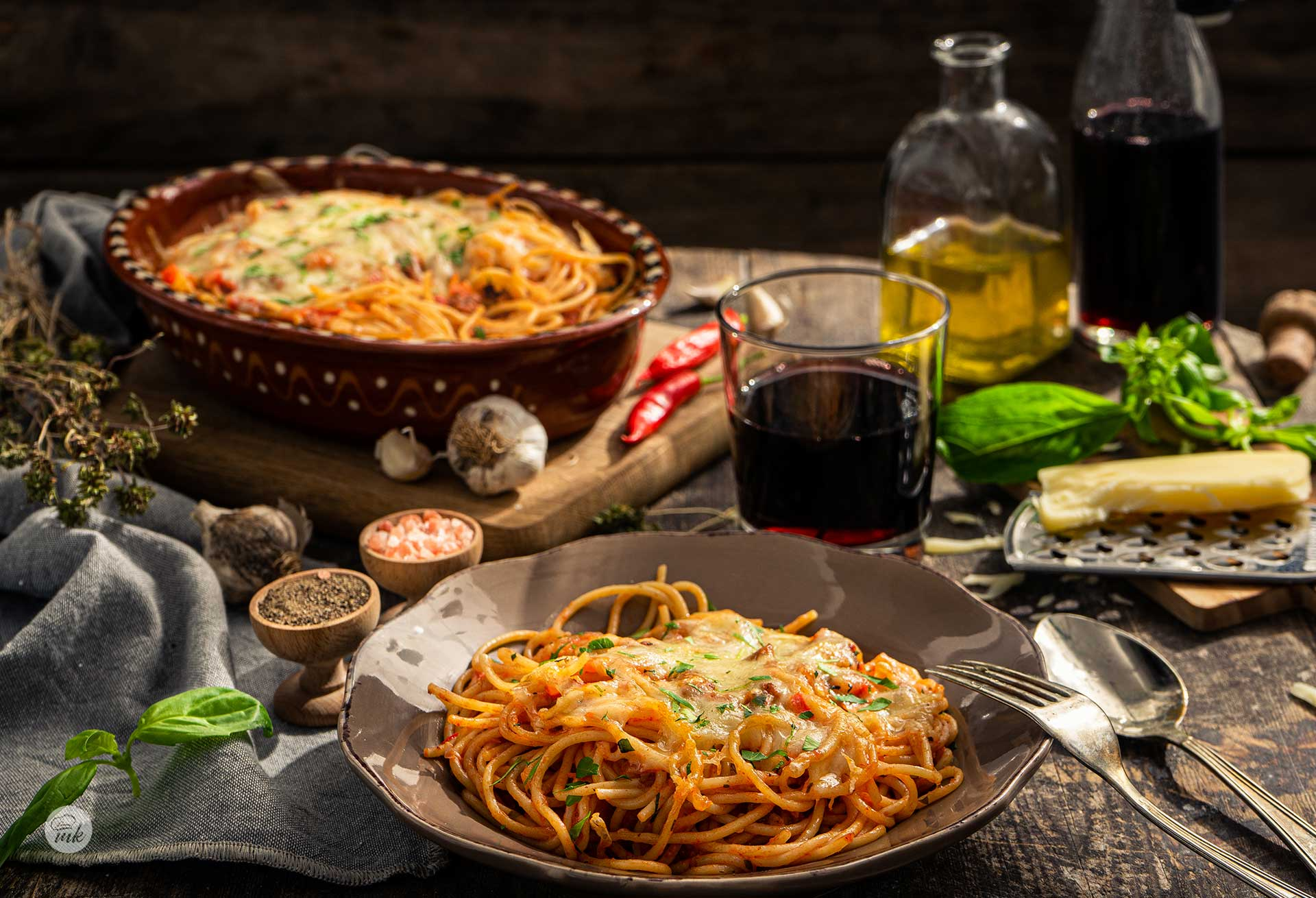 Спагети в гювече, севирани в чиния и гювече, с люти чушки, зехтин,чесън, кашкавал и босилек, снимани отстрани