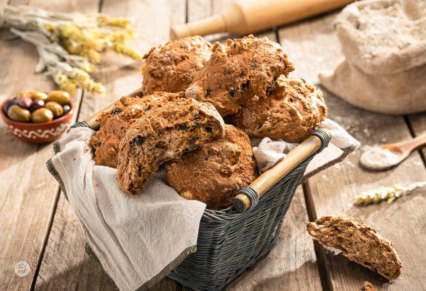 Бързи хлебчета с маслини, поднесени в панерчв, заснети отстрани