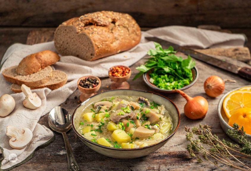 Бистра гъбена супа, сервирана в купа с хляб, лук, шарен пипер, снимано отстрани