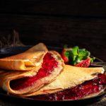 Палачинки от банани и стар хляб, завити в порция със сладко от горски плодове, заснети отстрани