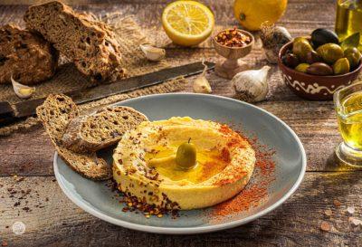Хумус, поднесен в купичка, поръсен с червен пипер и кимьон, аранжиран с маслинка и две брускети от франзела
