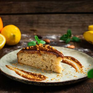 Бананов кекс, поднесен в единична порция в чинийка, аранжиран с глазура и пресни лимони