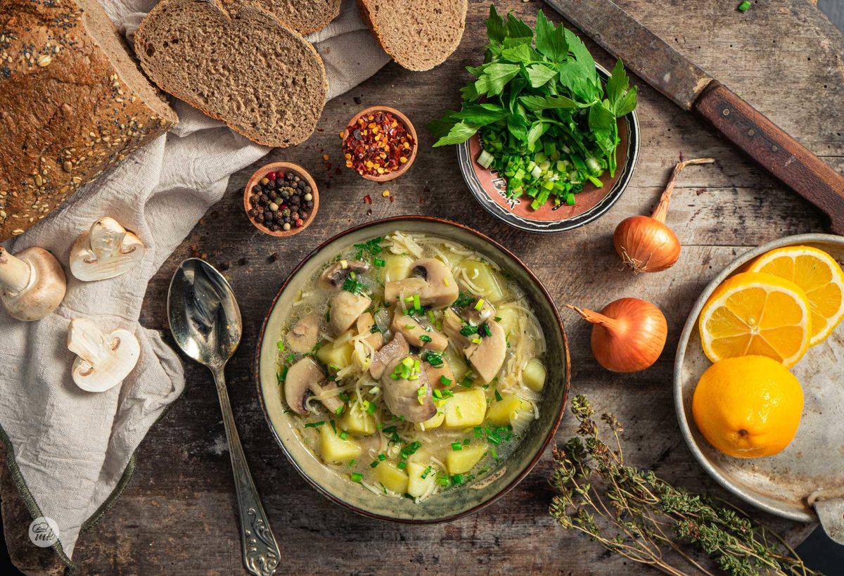 Бистра гъбена супа, сервирана в купа с хляб, лук, шарен пипер, снимано отгоре