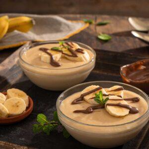 Бананов крем, заснет отстрани, поднесен в две купички, декориран с пресни банани и течен шоколад
