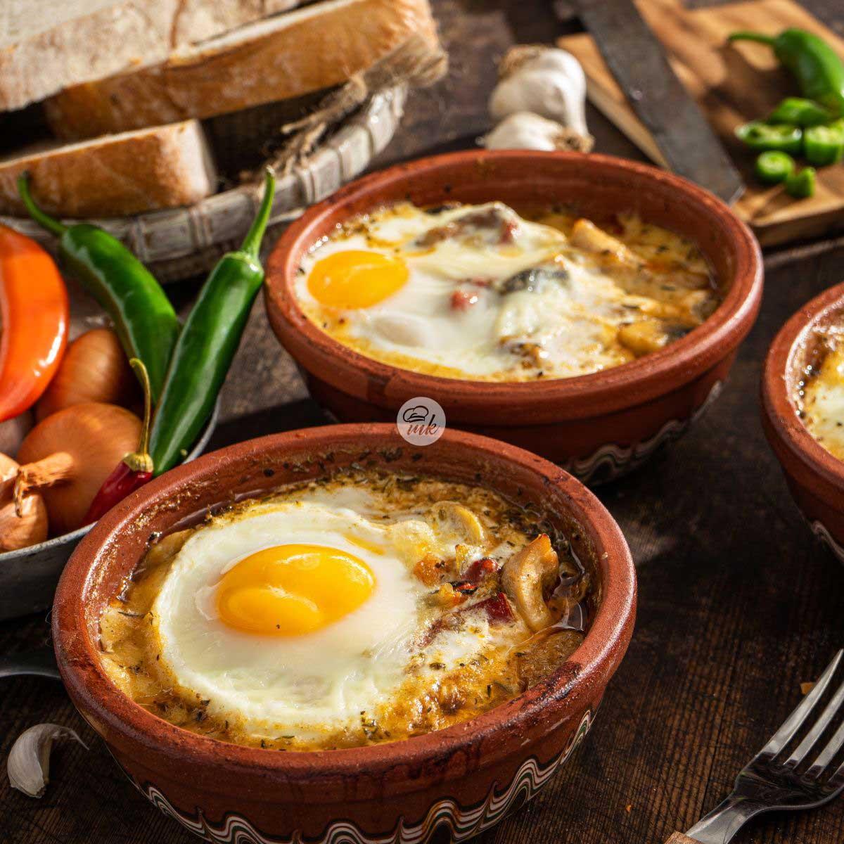 гювече със запечено отгоре яйце, декорирано с филийки черен хляб, чесън, пресни люти чушки и глава лук
