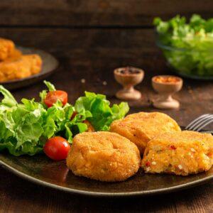 Вегетариански кюфтета поднесени в порция от 3, заснети отстрани и гарнирани със свежа салата и чери домати
