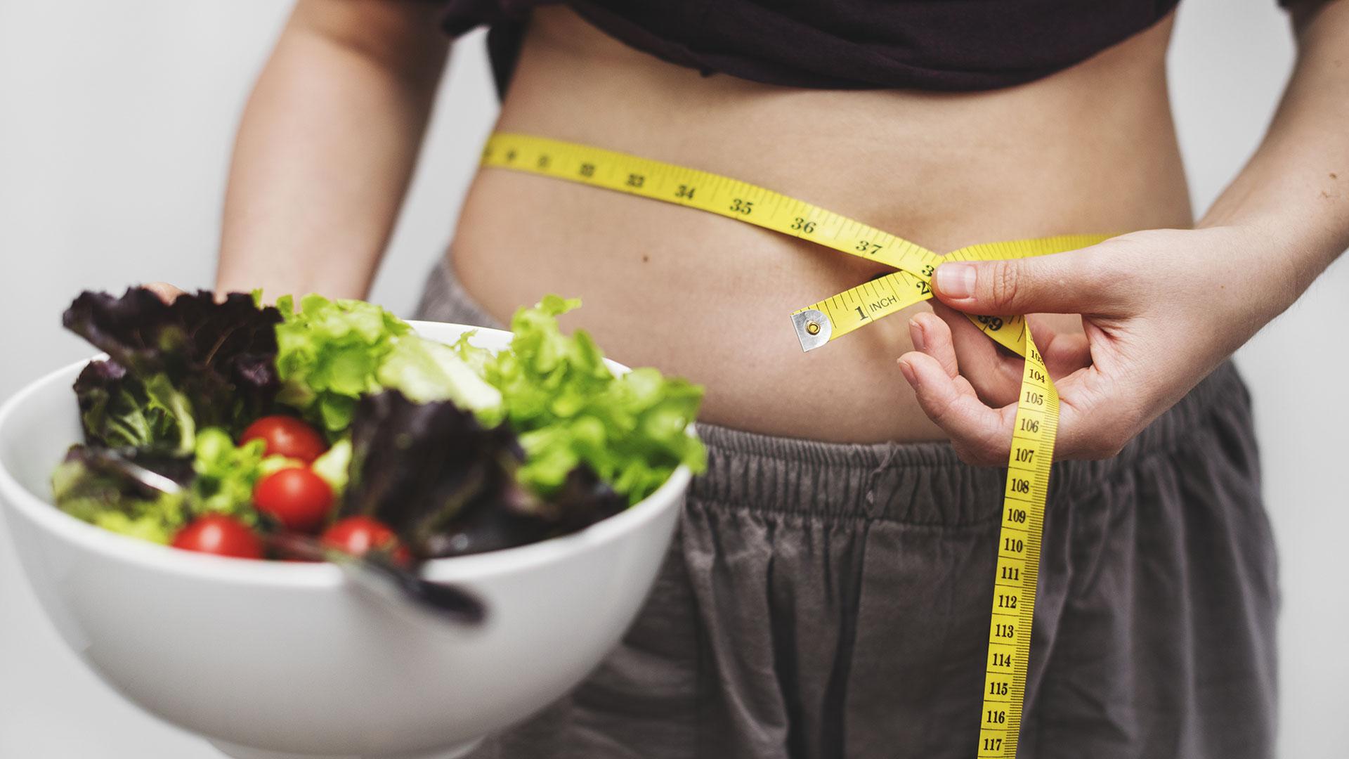 Жена с купа пресни желенчуци измерва талията си с шивашки метър