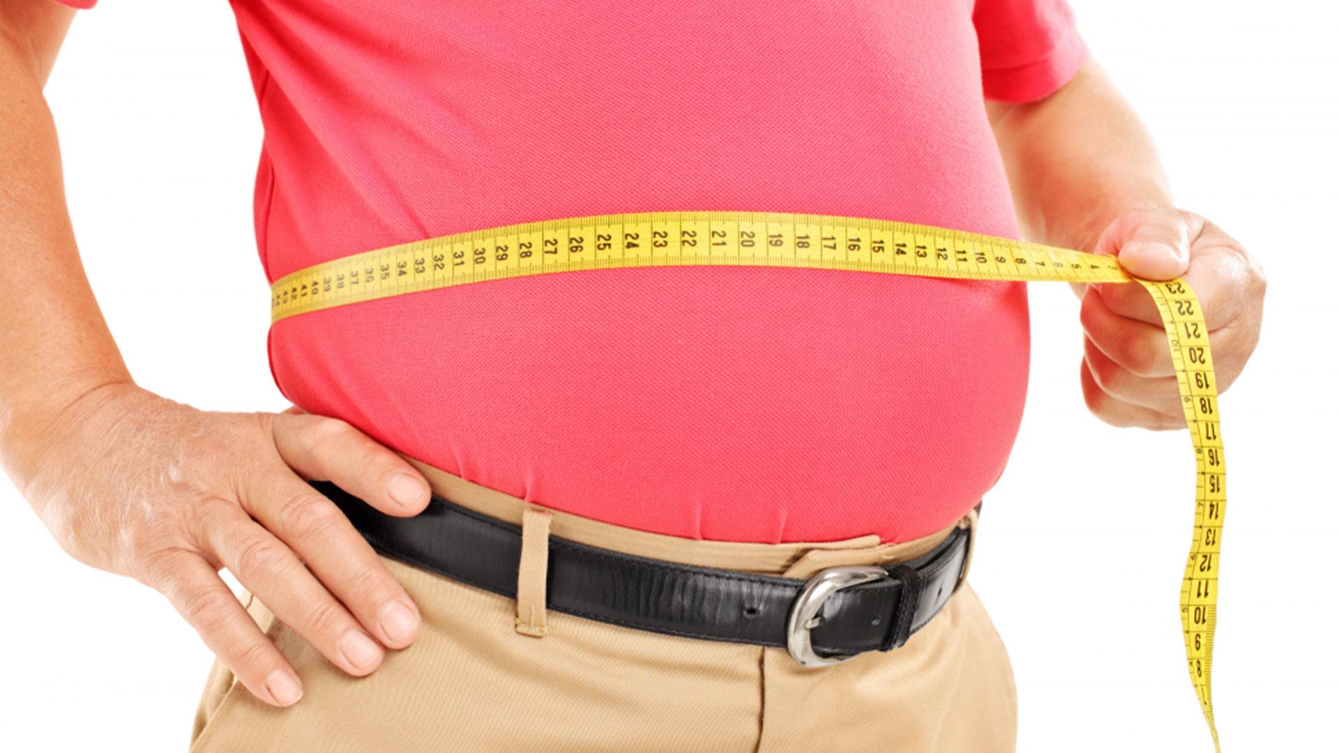 Мъж с наднормено тегло измерва с шивашки метър талията си