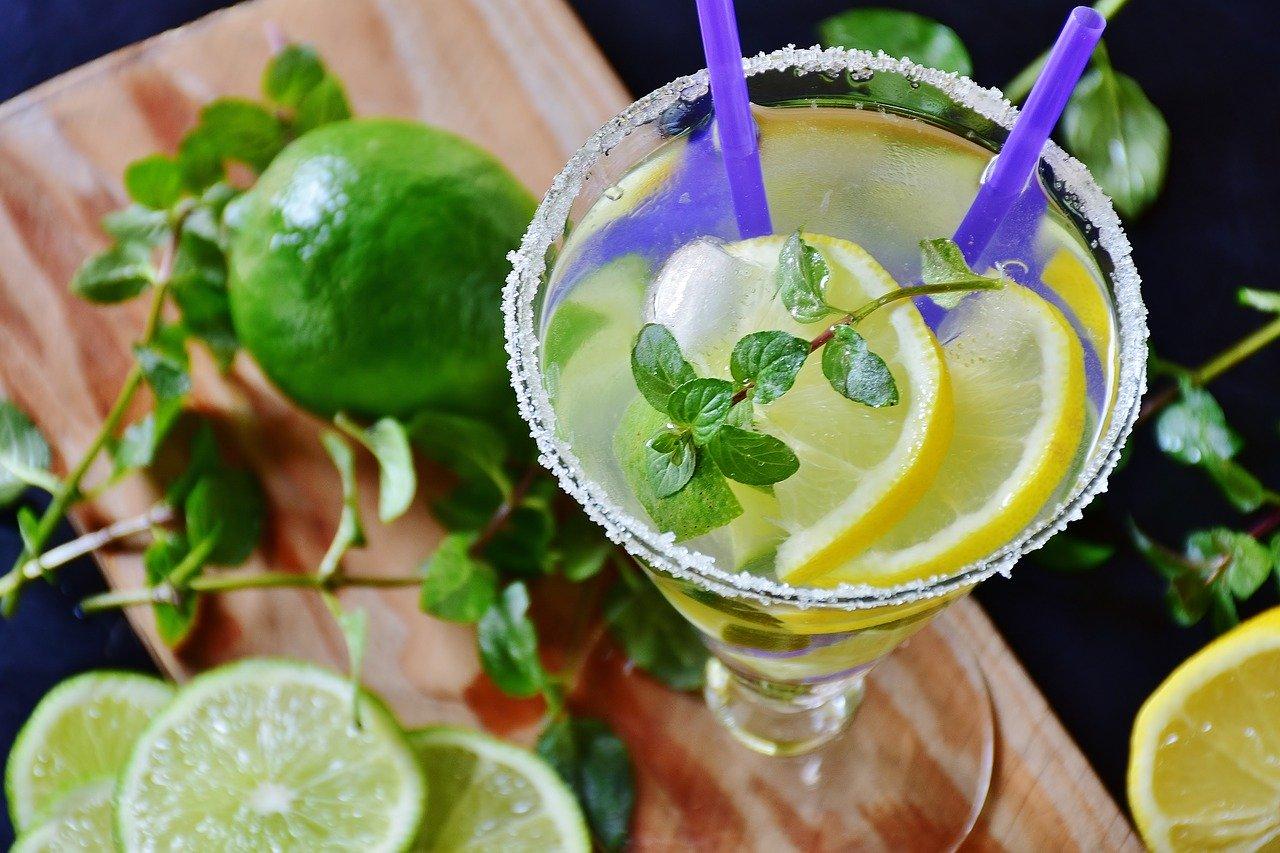 Лимонада с цели парченца лимон и стръкче мента, поднесена във висока шаша, със захар по ръба и две сламки