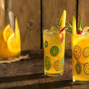 Две водни чаши с летен жълт коктейл и декорация