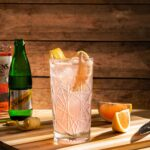 Кристална чаша с коктейл, розов джин и швепс