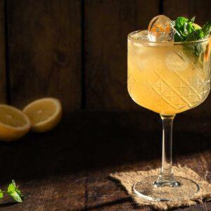 Кристална чаша със столче и жълт коктейл с ром