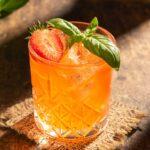 Кристална чаша без столче, с оранжев коктел и листа босилек