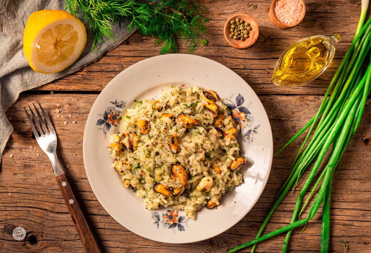 Поглед отгоре на чиния с миди с ориз по гръцки и декорация от пресни подправки