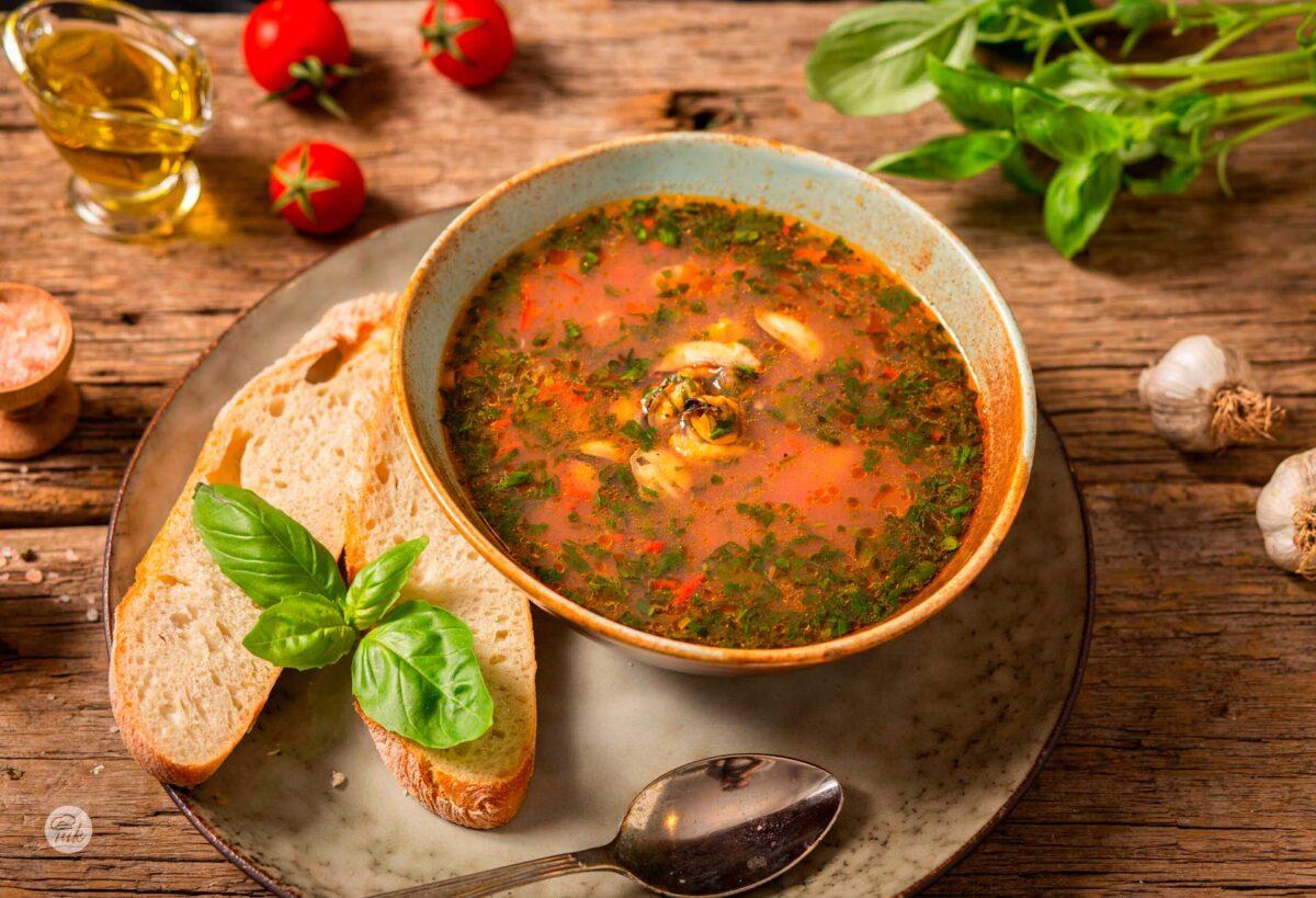 Купа със супа от миди, филийки хляб и декорация отпресни подправки и зеленчуци