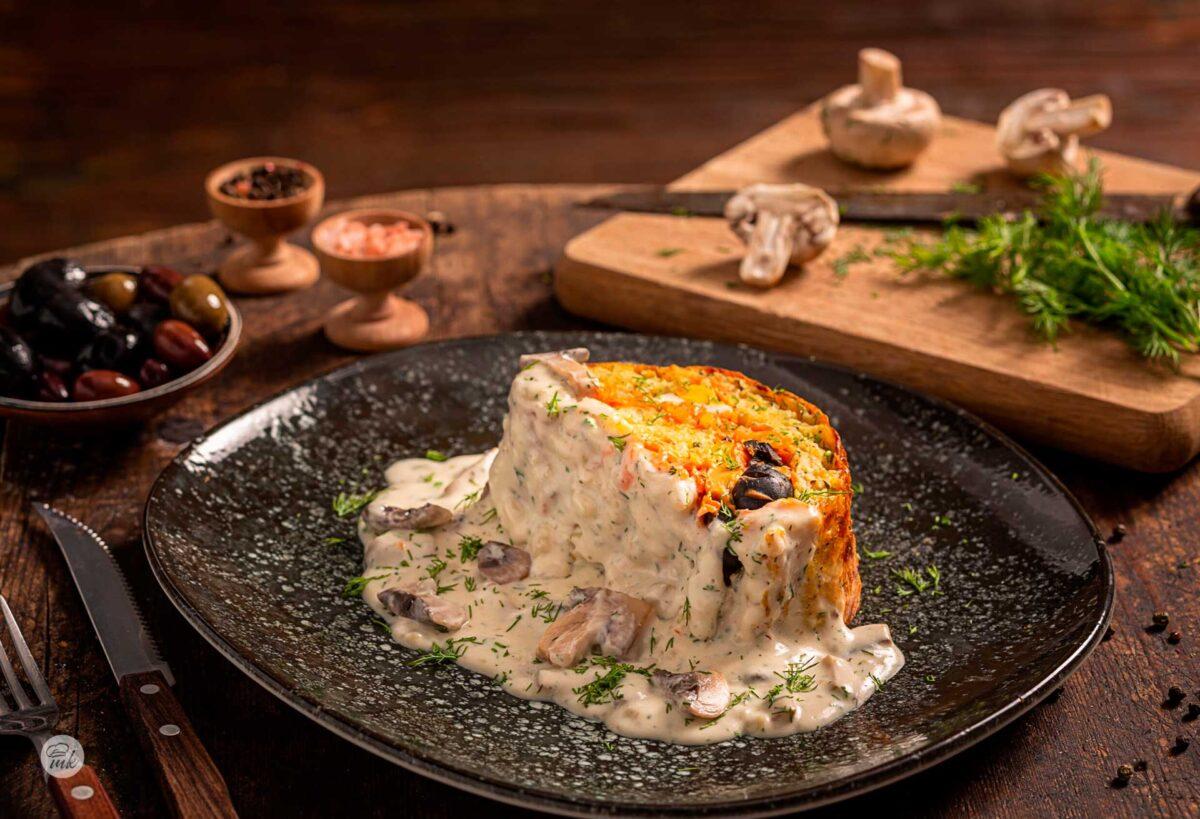 Разрязано парче от картофено руло с гъби в тъмна чиния и декорация от пресни продукти
