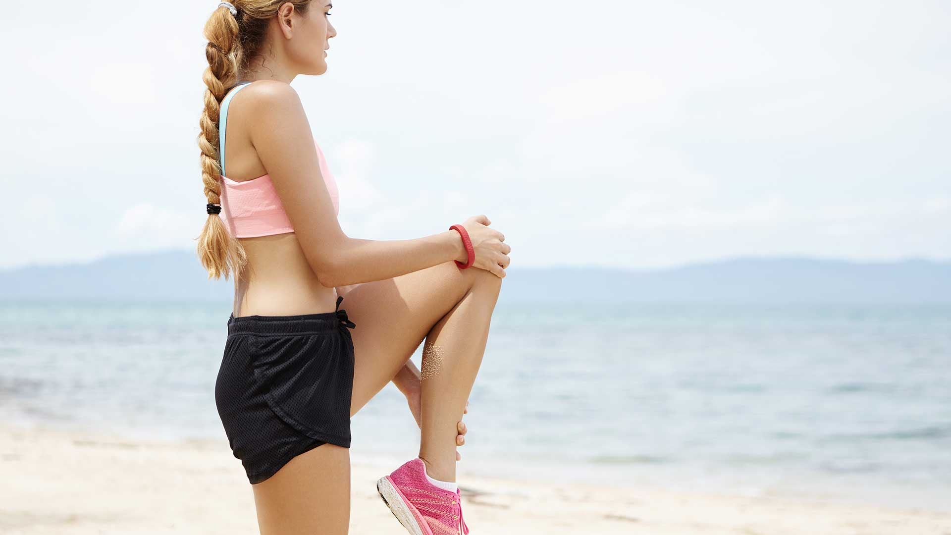 Млада жена загрява на плажа преди спорт
