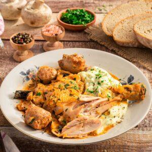 Пиле по ловджийски, поднесено с картофено пюре. Снимано отпред с филии хляб, пресни гъби, черен пипер на зърна и едра сол