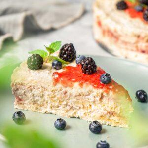 Бисквитена торта с маскарпоне и сладко от малини, сервирано в чиния с боровинки, между листенца мента, снимано отстрани
