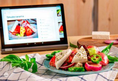 гръцка салата в синя чиния, със сирене и таблет, снимано отстрани