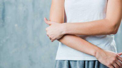 Жена с болка в лакътя, придържа с ръка