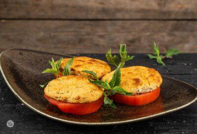 Кюфтета от крема сирене, поднесени върху кръгове домат и украсени с пресен джоджен