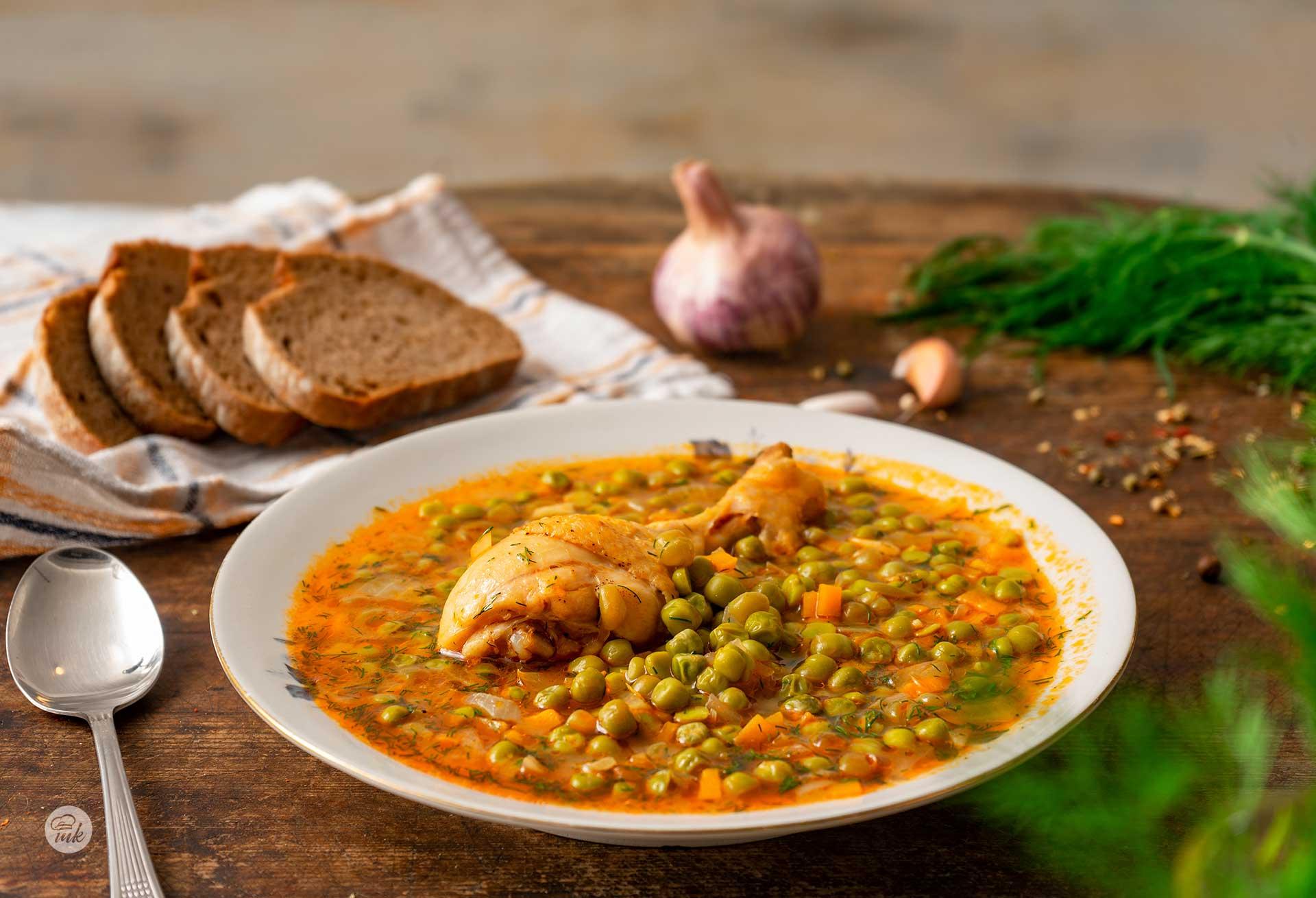 пилешка яхния с грах, сервирана в дълбока чиния с филийски хляб на заден фон, снимано отстрани