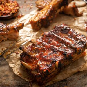 свински ребърца с барбекю сос, сервирани върху хартия за печене, снимани отстрани
