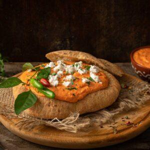 Урнебес със сирене отгоре, върху дървена кръгла дъска, снимано отстрани