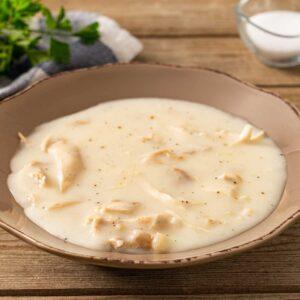 Бяла каша с пилеко месо, сервирана в дълбока чиния, снимано отстрани