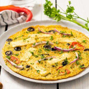 Омлет с чушки, лук и маслини, поднесен в бяла чиния