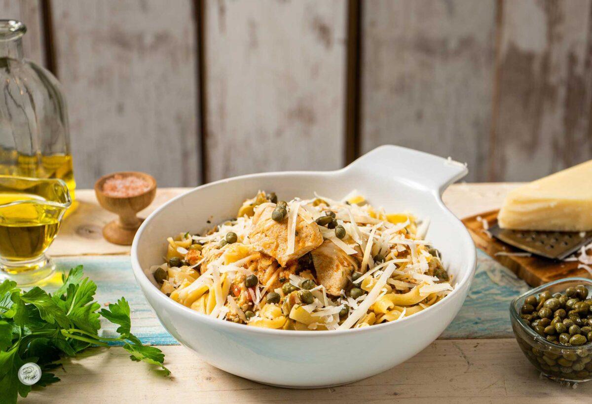 Порция пиле с каперси, маслини и паста, сервирана в бяла купичка