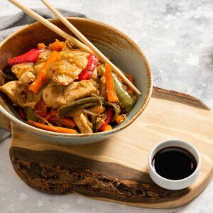 Порция пиле със зеленчуци, мед и соев сос, поднесено с купичка соев сос и дървени клечки за хранене