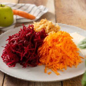 Салата от цвекло, морков и ябълка, сервирани на три купчинки в чиния, снимана отстрани