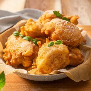 Ябълкови бухтички, сервирани върху хартия за печене в дълбока чиния, с листена мента и пудра захар, снимано отстрани