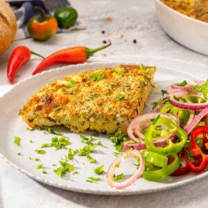 Порция яйца със сирене и кашкавал на фурна, поднесени с нарязани на шайби чушки и червен лук