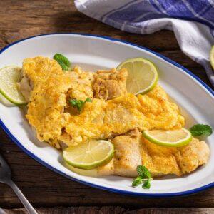 Филе от бяла риба с горчица, поднесено в бяла продълговата чиния, снимано отстрани