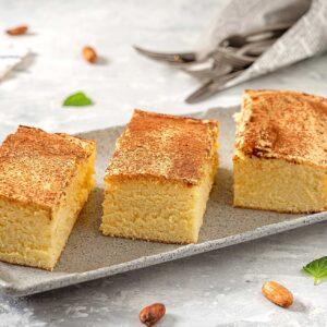 Три правоъгълни парчета кекс 14 лъжици, поръсени с пудра захар, поднесени в правоъгълна чиния