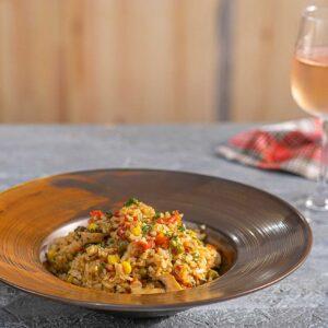 Порция ориз със зеленчуци в кафява чиния и чаша розе