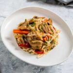 Порция оризови спагети със свинско месо и зеленчуци, поднесено в бяла чиния