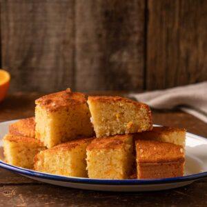 Кейк с портокалови корички, нарязан на парчета и поднесен в бяла чиния със син кант