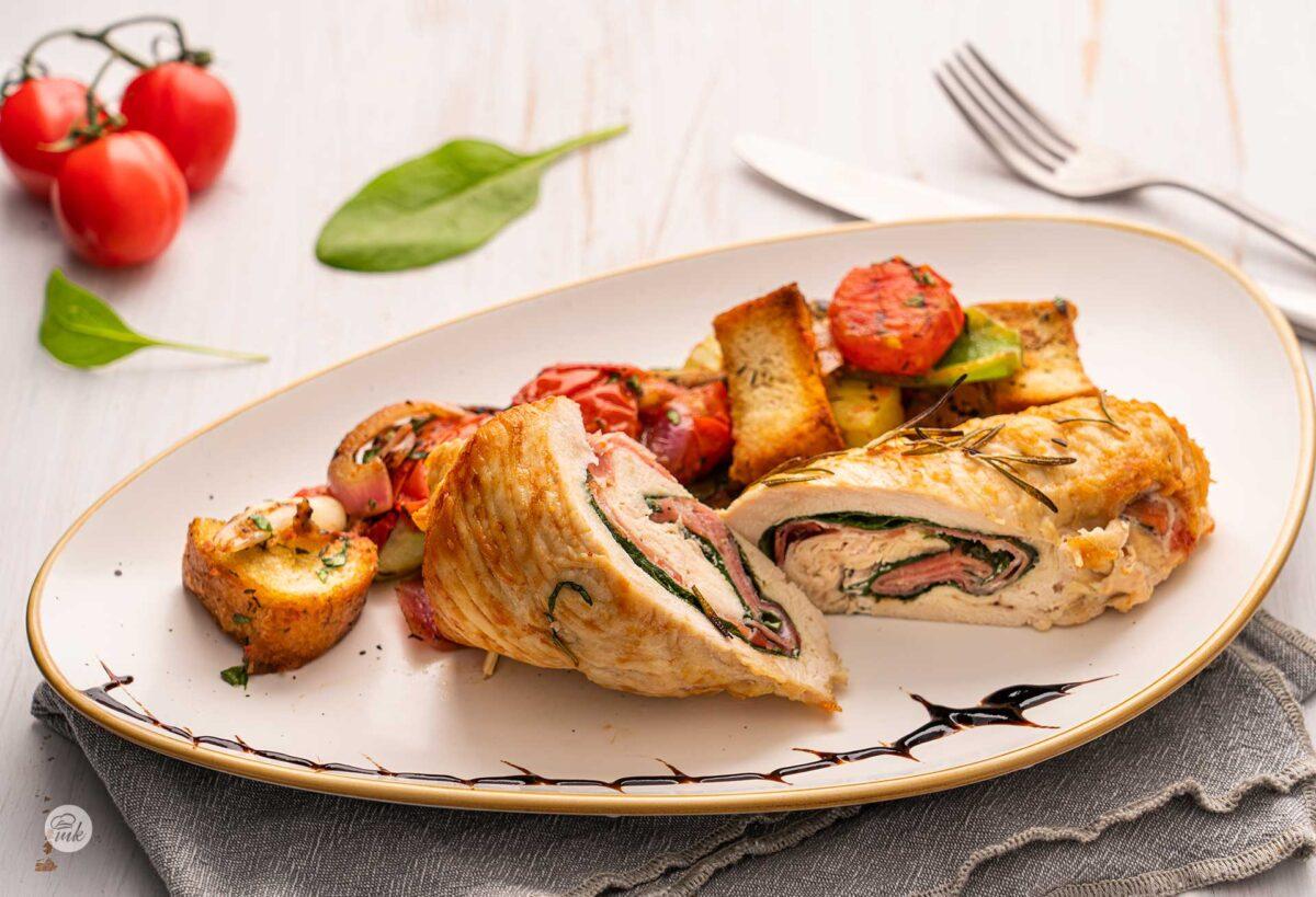 Пилешко руло с прошуто и спанак в бяла чиния с гарнитура и украса, снимано отстрани
