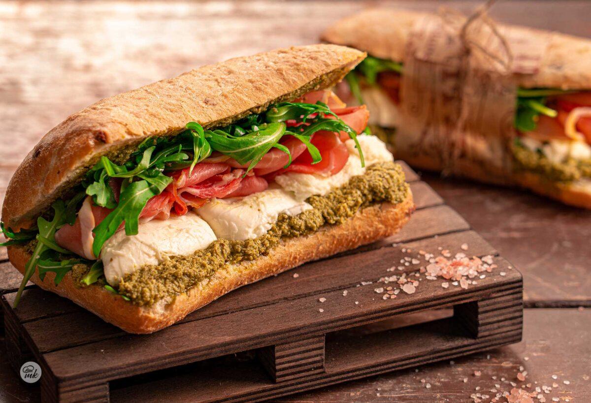Сандвич с прошуто и моцарела върху малко дървено пале, сниман странично