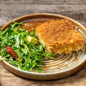 Порция шунка със сирене и яйца на фурна, поднесена със зелена салата