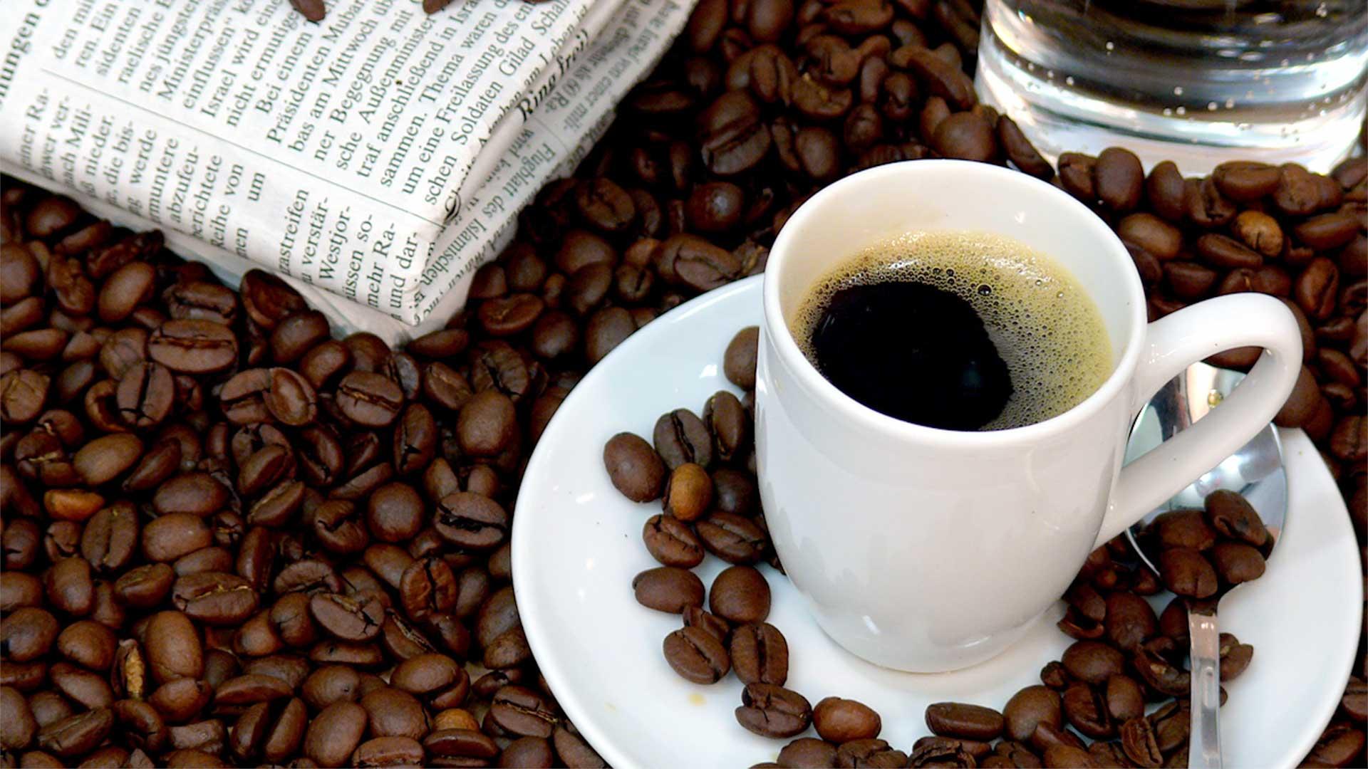 Чаша кафе върху плътен слой кафеени зърна и сгънат вестник отляво