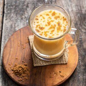 яйчен пунш, гарниран с настъргано индийско орехче, поднесен в стъклена чаша с дръжка