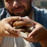 Мъж с наднормено тегло яде хамбургер