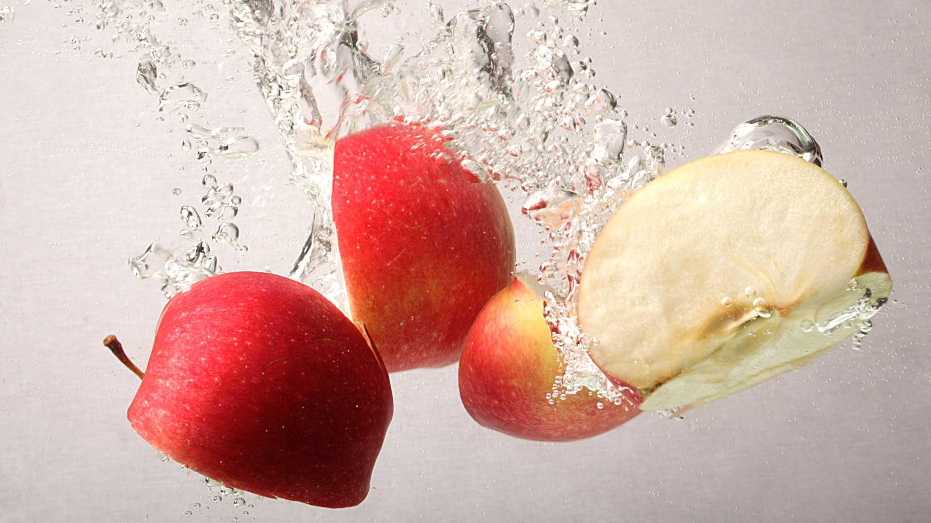 парчета червена ябълка във вода