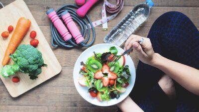 Момиче с чиния с плодеве и зеленчуци на фона на уреди за спорт